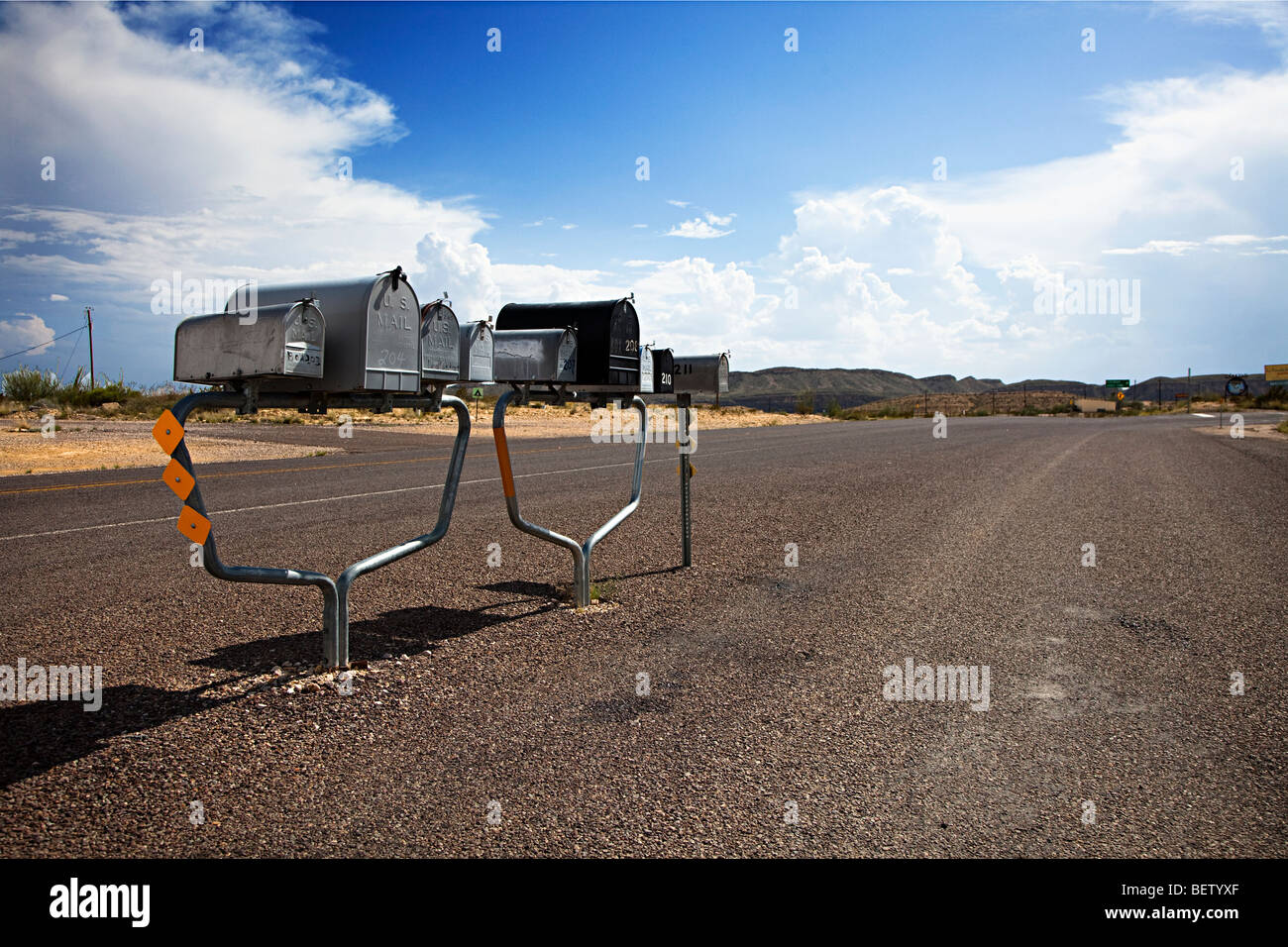 Line of mailboxes in middle of empty road Terlingua Texas USA - Stock Image