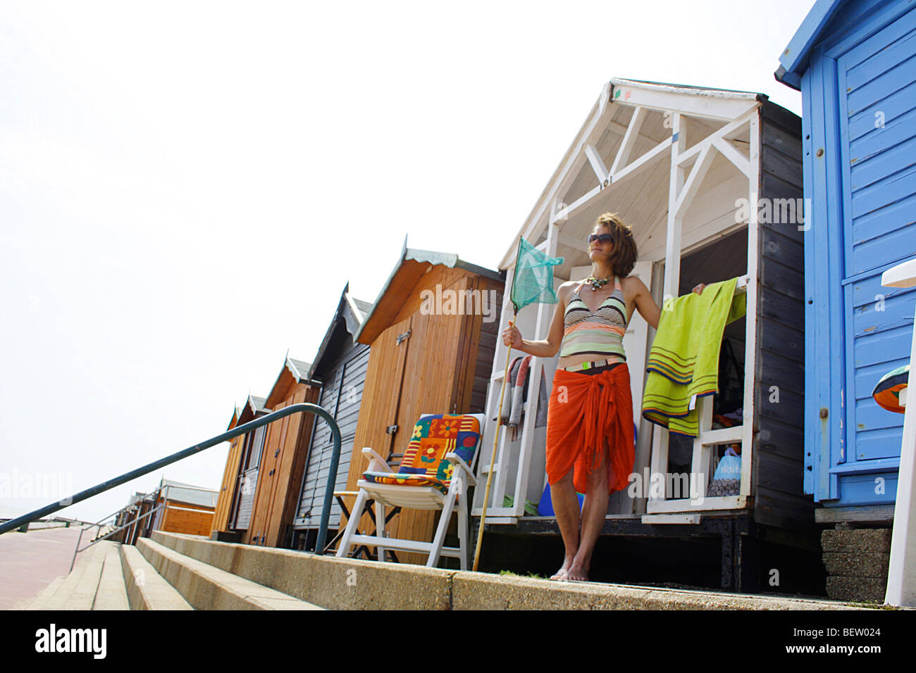 woman standing outside an English beach hut on an English summer's day - Stock Image