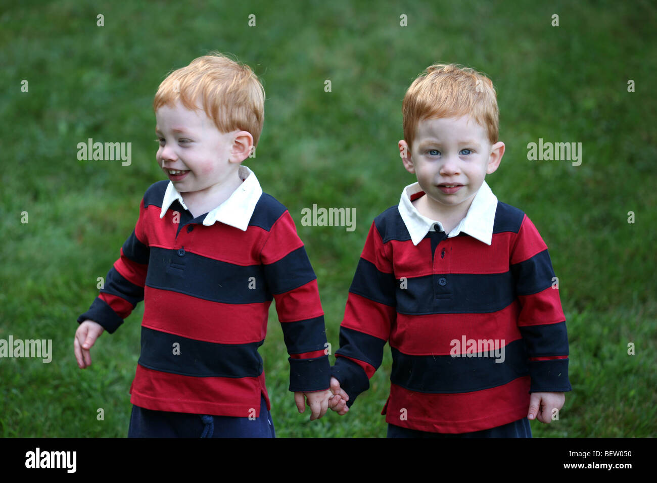 Twin baby boys holding hands outside - Stock Image