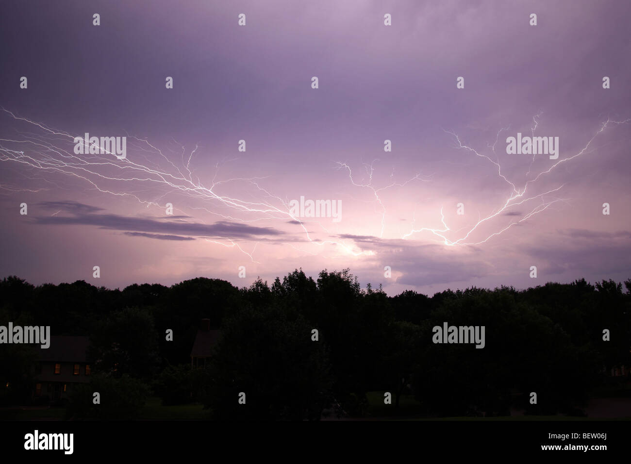 Lightening strike over woods and houses - Stock Image
