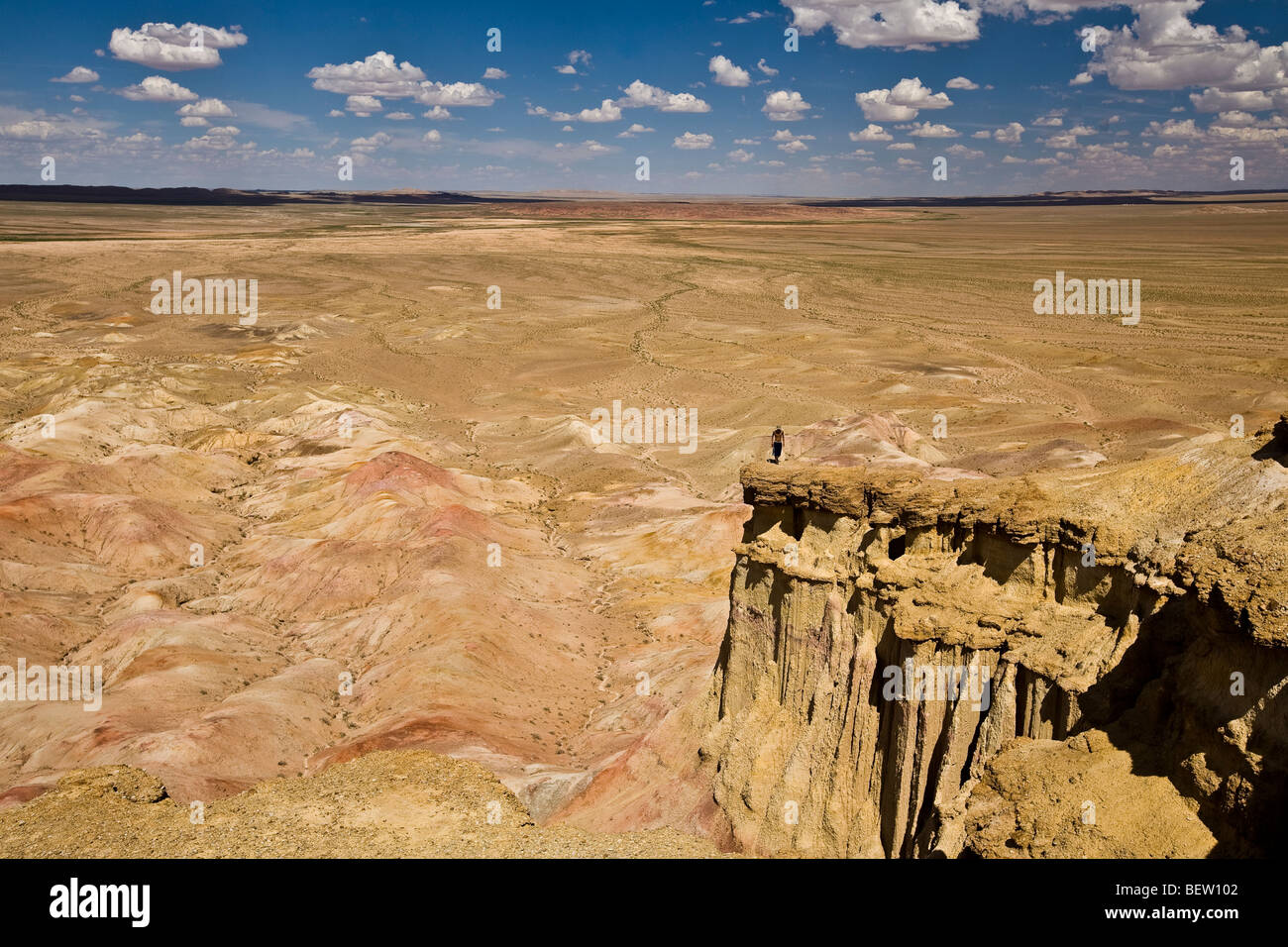Man standing on edge of a high cliff overlooking the Gobi desert Mongolia - Stock Image