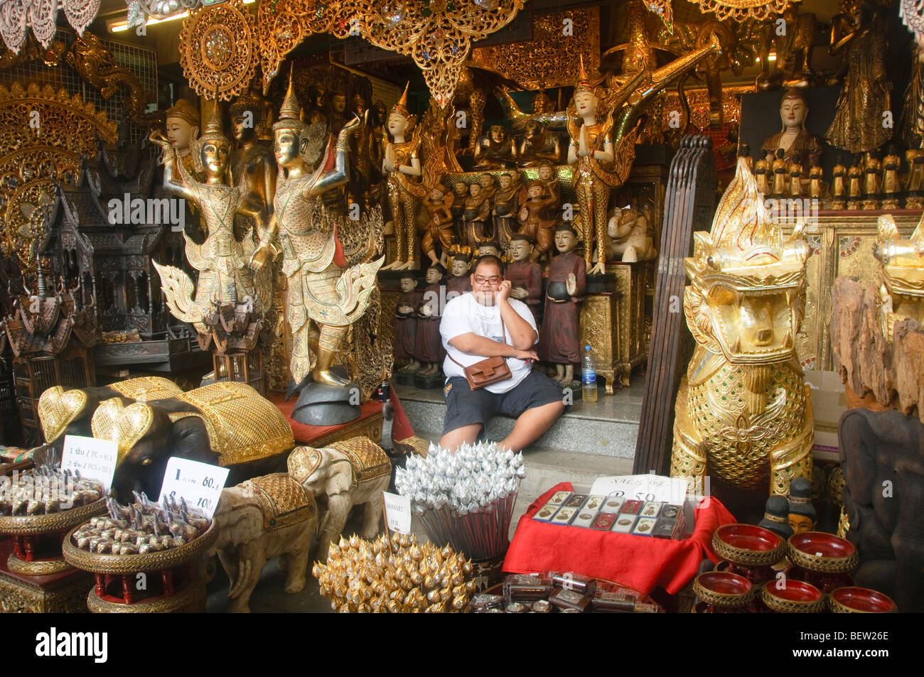 merchant sitting amongst his Buddha statues at the Chatuchak Weekend Market in Bangkok Thailand - Stock Image