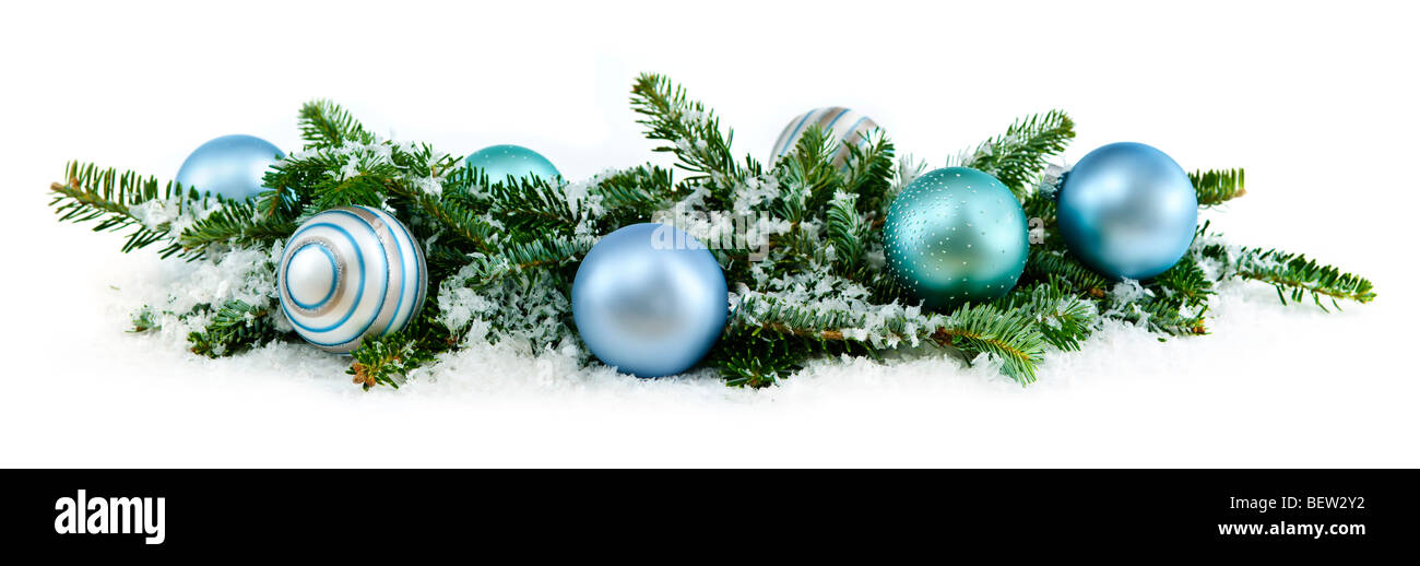 Many Christmas decorations laying in pine branches and snow - Stock Image