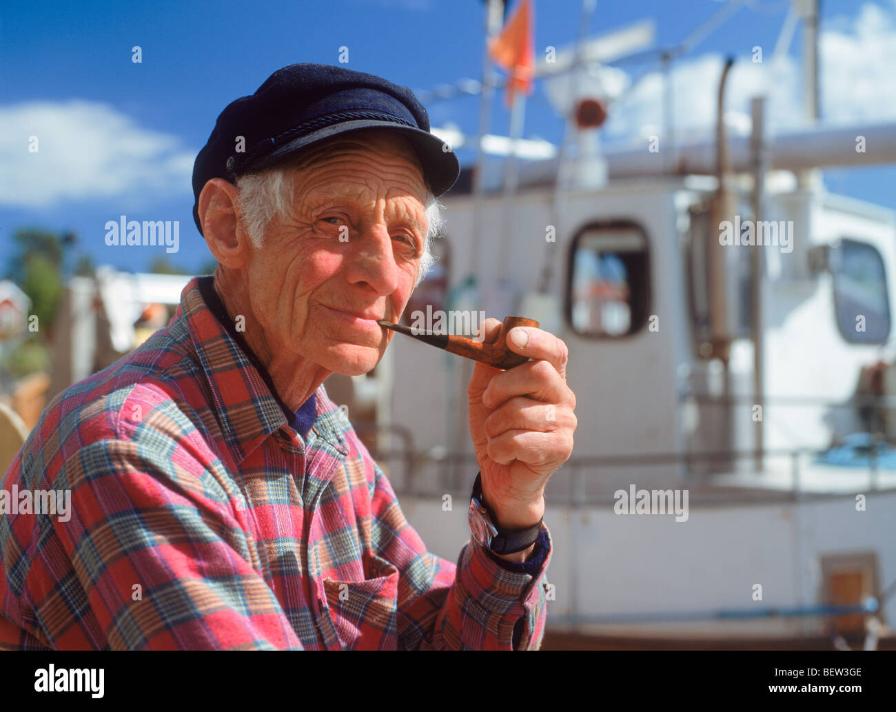 elderly fisherman with pipe and fishing boat at kuggoren in baltic