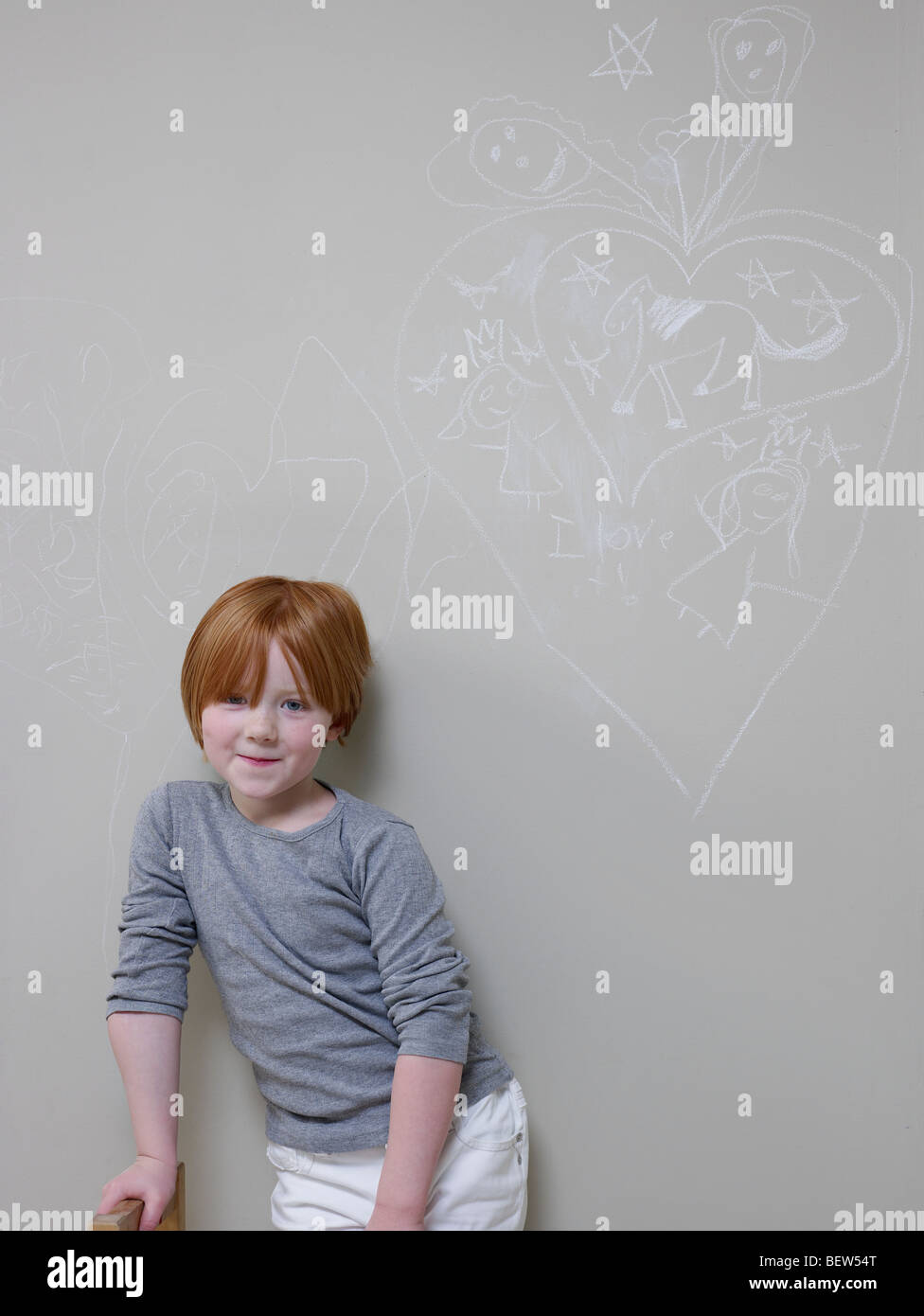 7-8 Year old girl stands below chalk drawing on wall Stock Photo