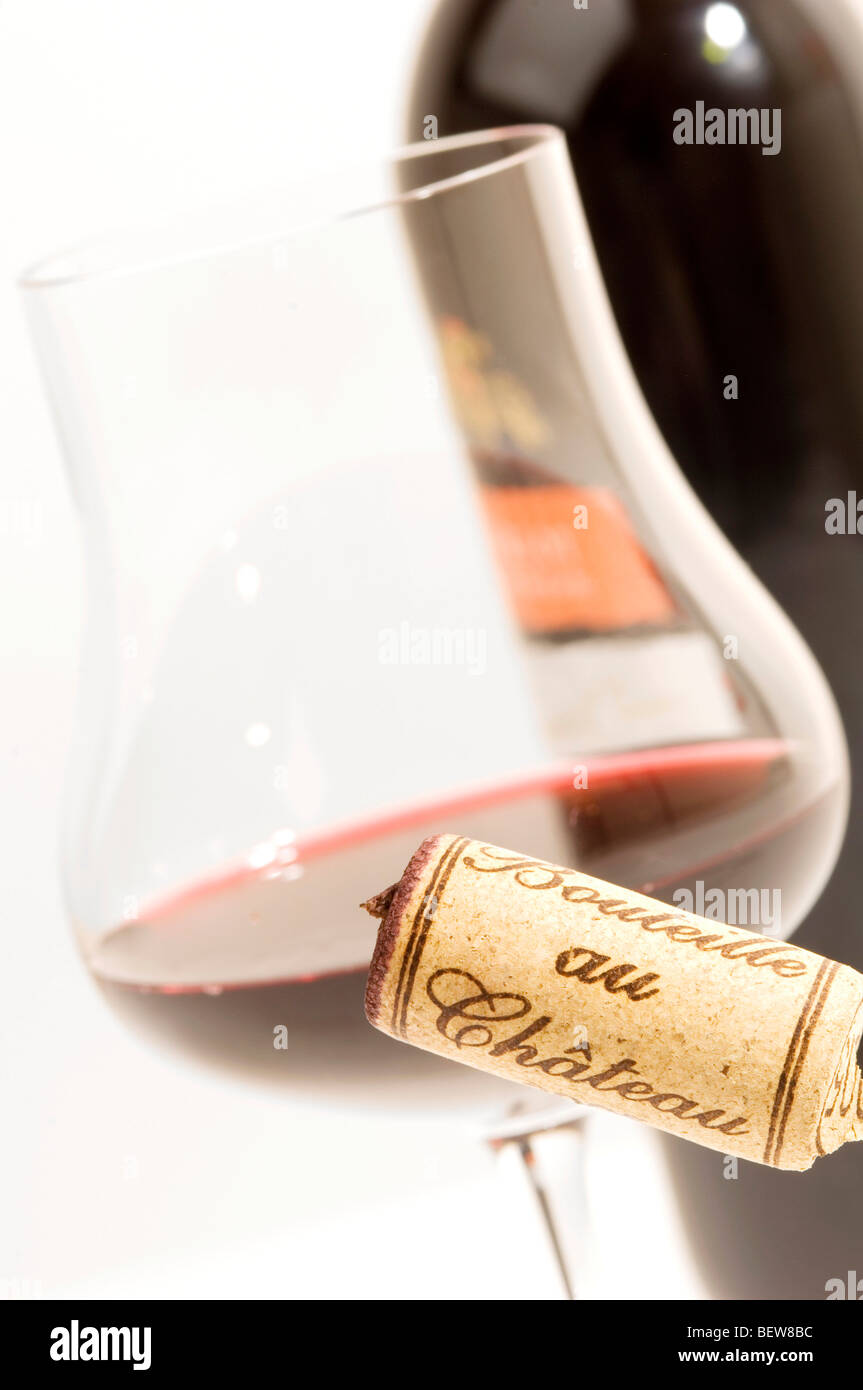 Claret glass and corkscrew in front of wine bottle, close-up - Stock Image