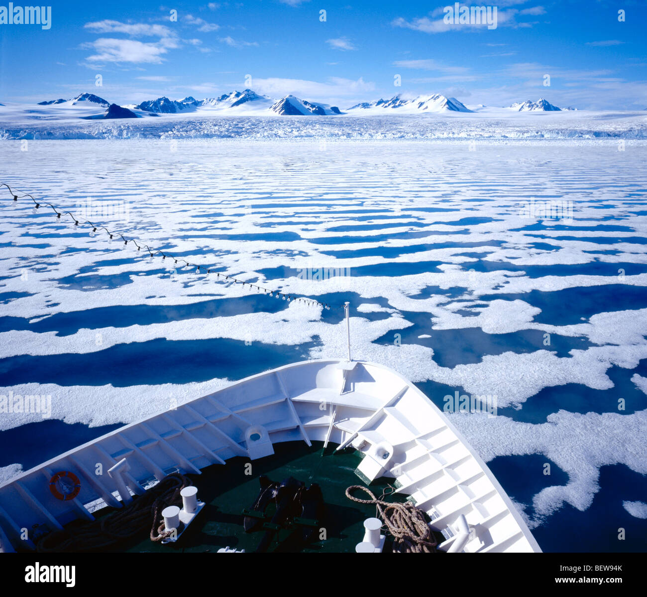 Cruise ship moving through sea covered with icebergs Stock Photo