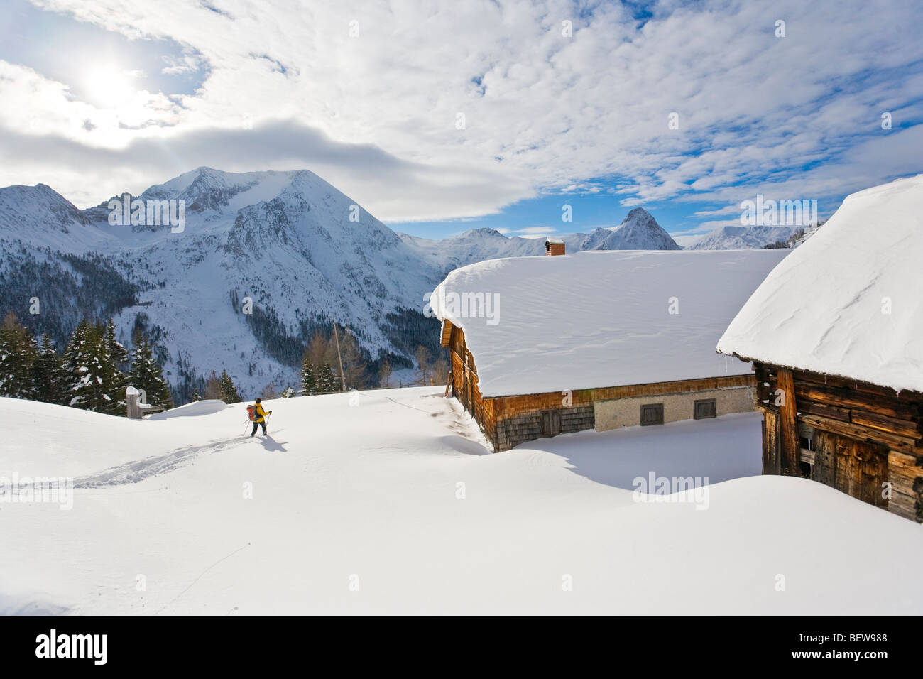 Woman with skis on a snowy mountain pasture with timber houses, Zederhaus, Salzburg, Austria - Stock Image