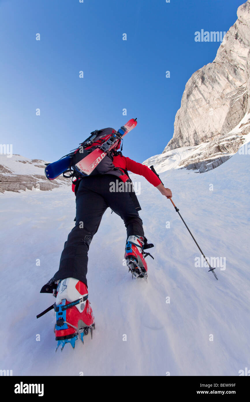Person climbing on a snowy mountain skis, Berchtesgaden, Germany, low angle view - Stock Image