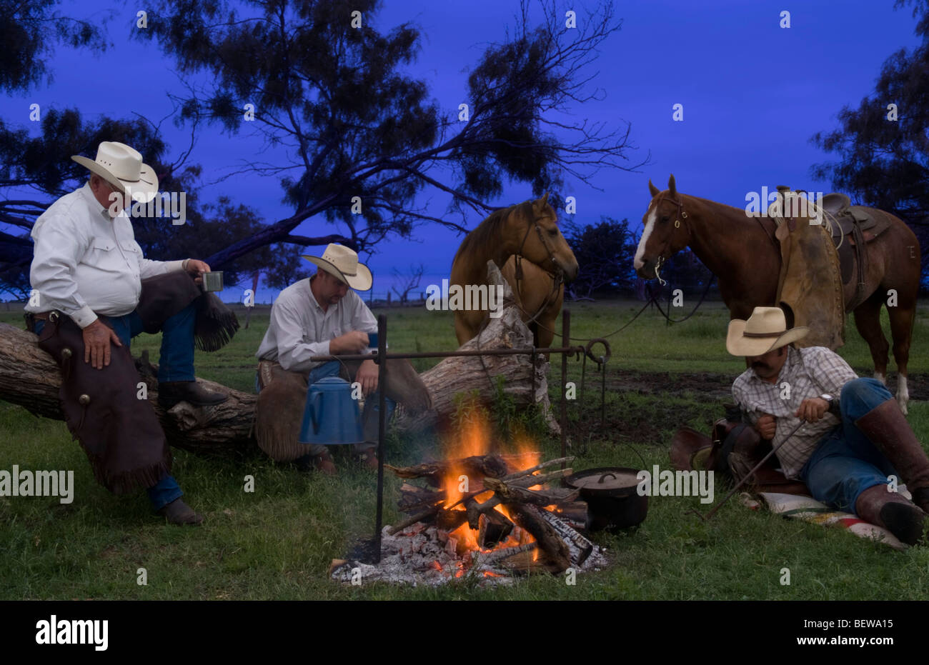 Cowboys resting beside a campfire - Stock Image