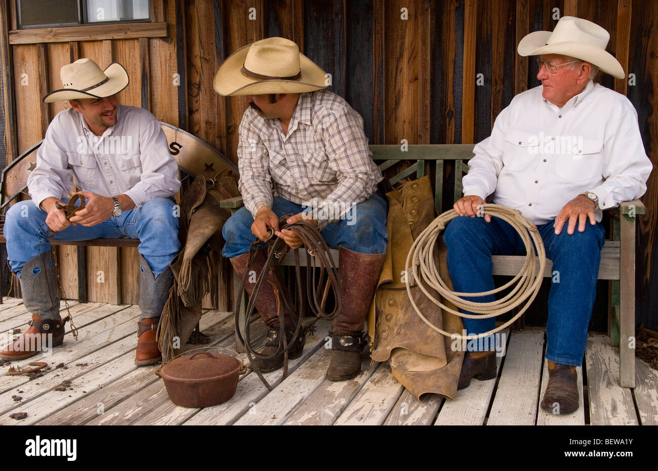 Three cowboys sitting side by side, full shot, USA - Stock Image