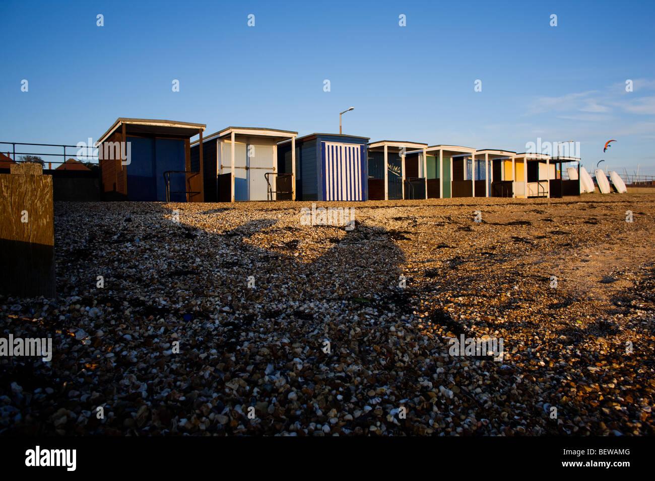 Beach huts on the stoney beach at Shoeburyness in the late autumn sunshine,  near Southend on Sea, Essex, UK - Stock Image