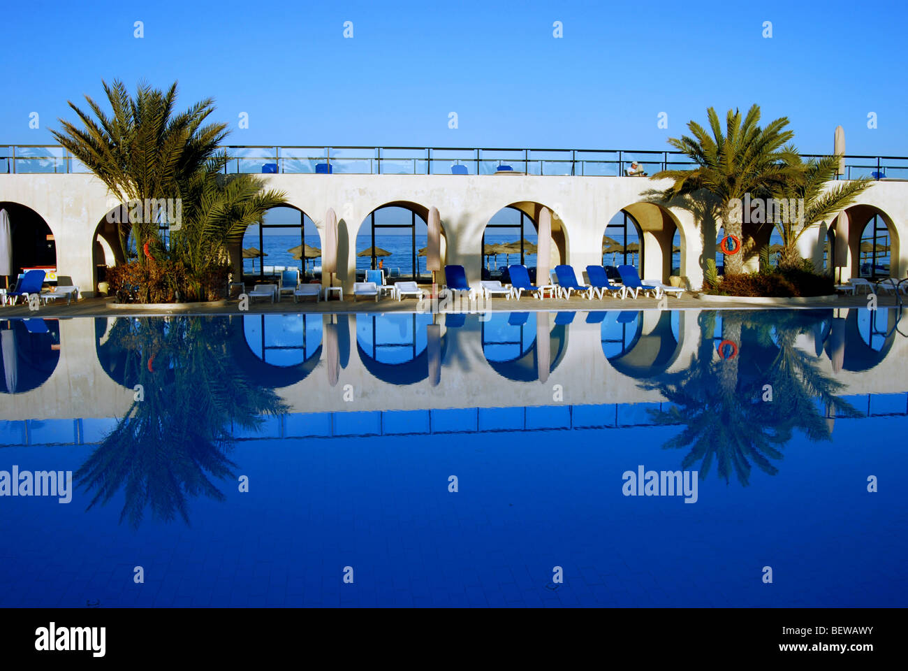 Reflection of arcades and palms on water surface of a swimming pool, Djerba, Tunisia - Stock Image