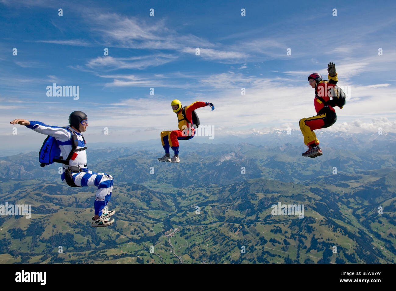 three people doing parachute jumping, full shot - Stock Image