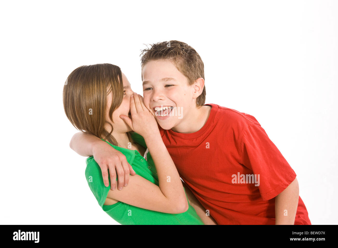 girl whispering something in a boy's ear Stock Photo