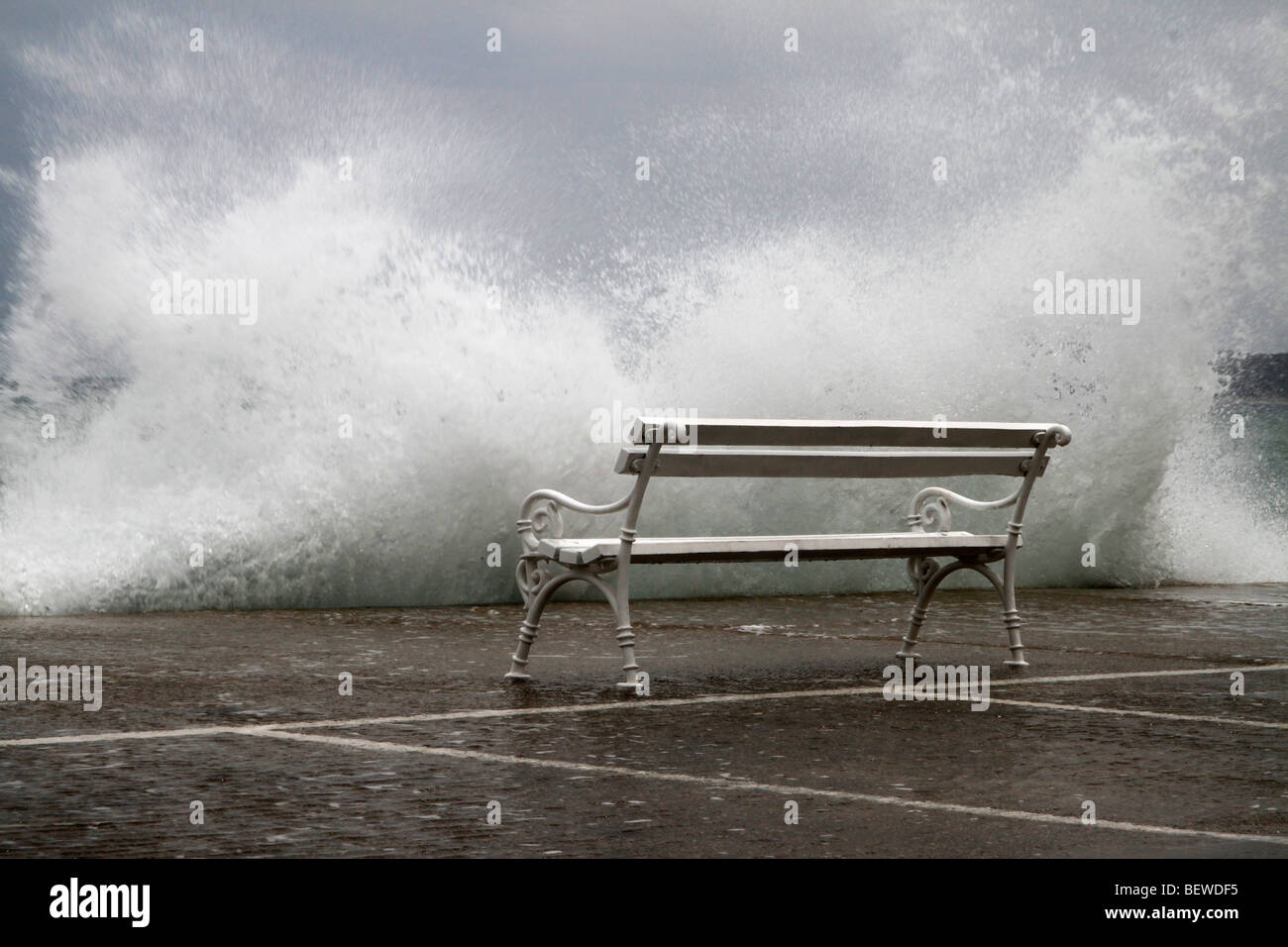 Unoccupied bench in front of massive wave chrashing against quay wall, Vodice, Croatia - Stock Image