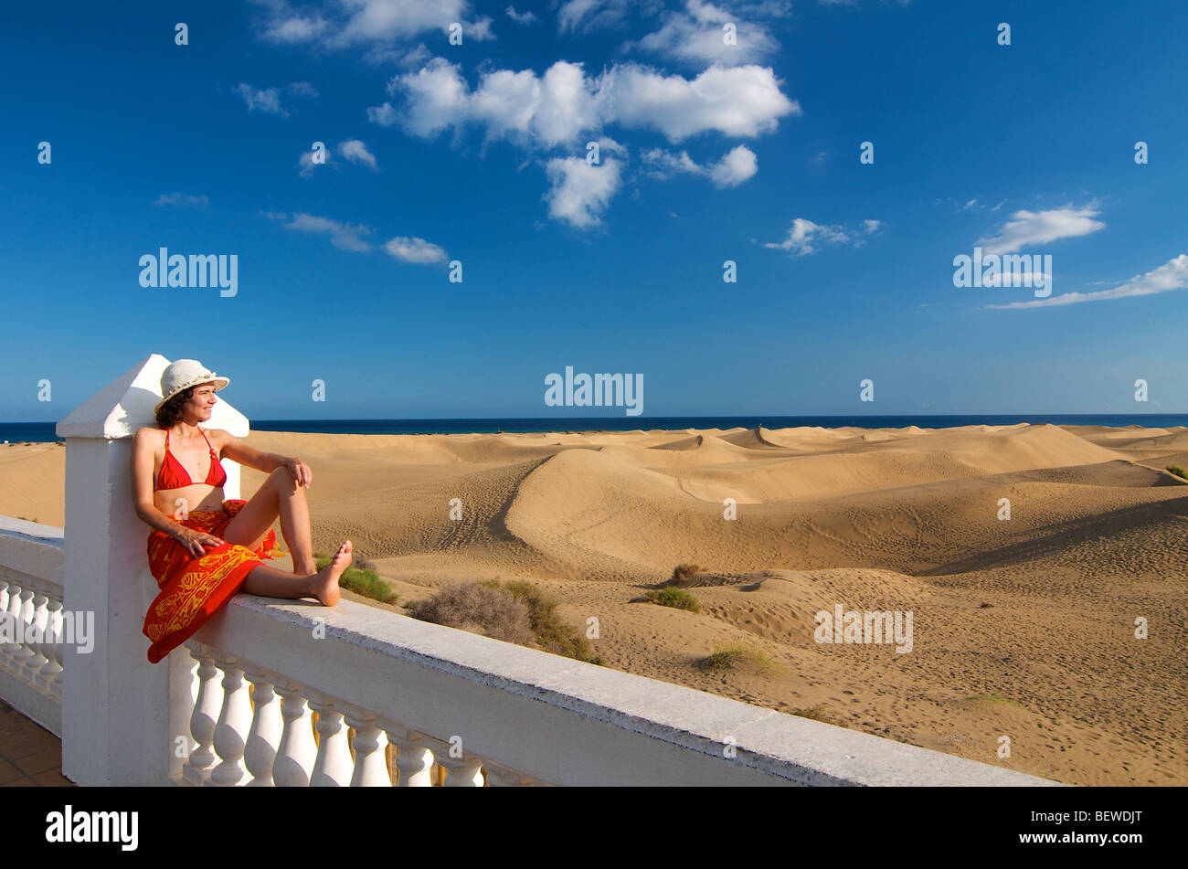 Woman sitting on a fence looking at the sand dunes, Maspalomas, Gran Canaria, Spain - Stock Image