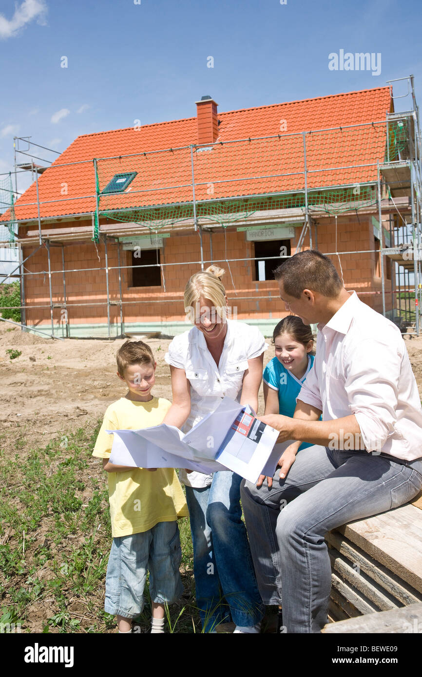 Family with two children looking at a plan in front of a house under construction Stock Photo