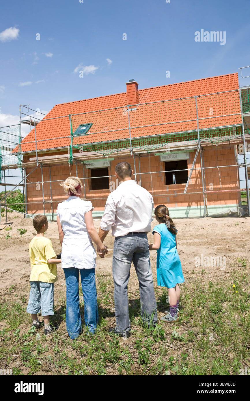Family with two children looking at house under construction, rear view Stock Photo