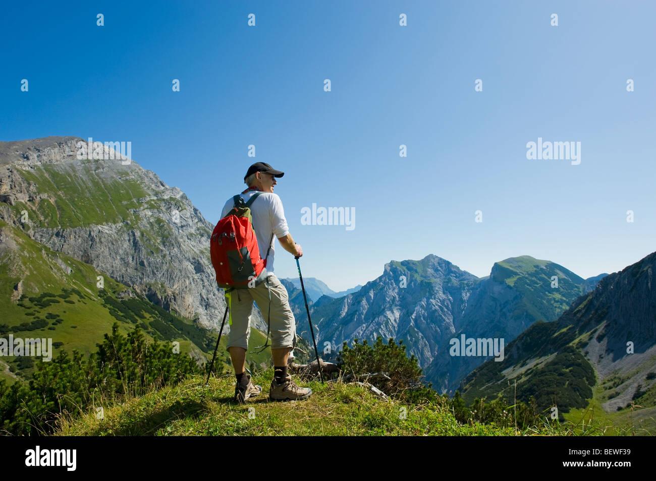walking walker in the mountains alpes karwendel austria walking stick mountain hiker rambler 1 man lonely alone - Stock Image
