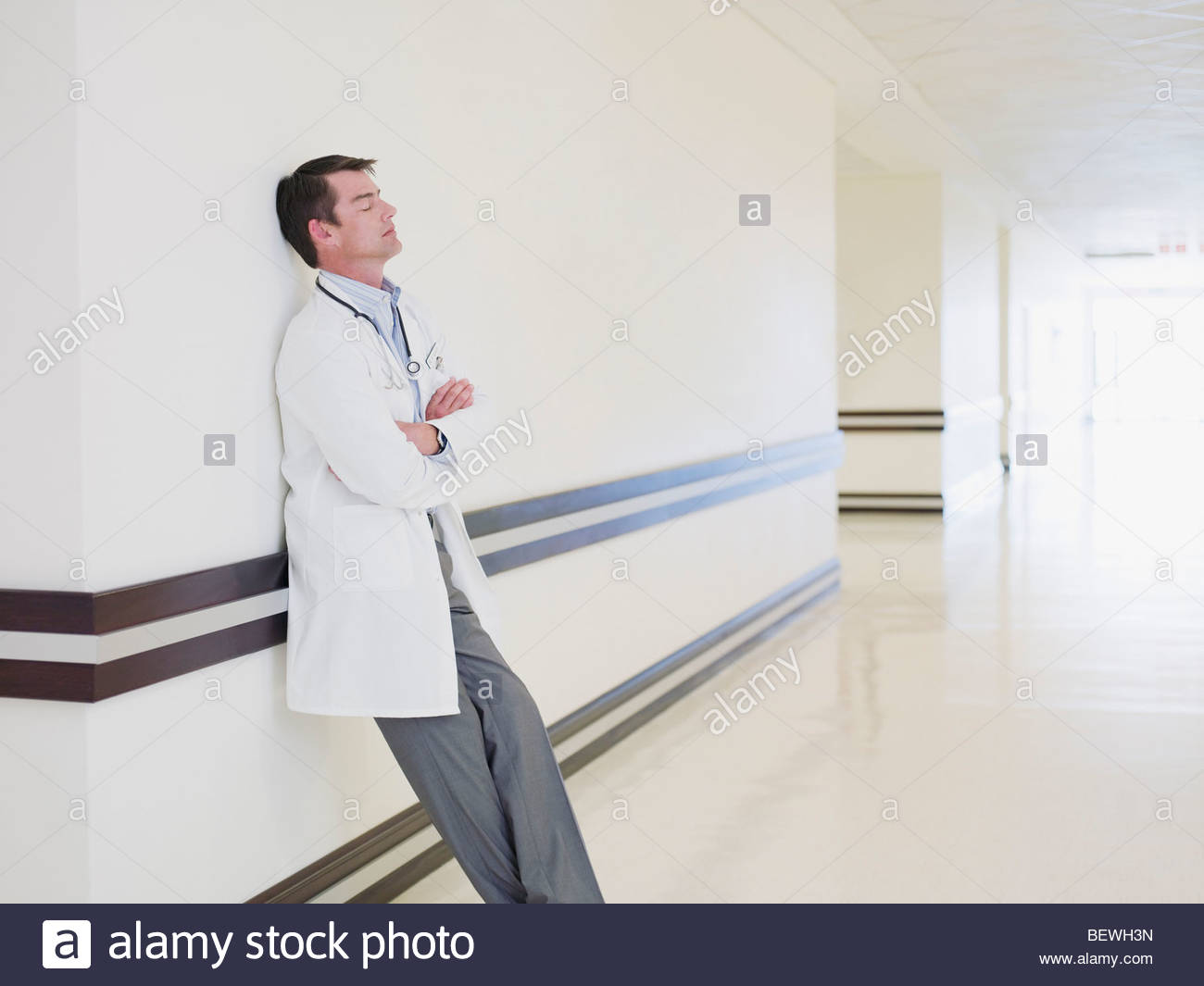Tired doctor leaning in hospital corridor - Stock Image