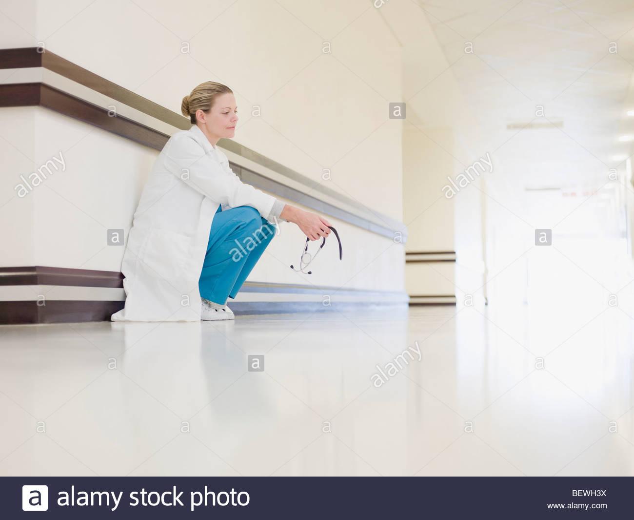 Doctor squatting in hospital corridor - Stock Image