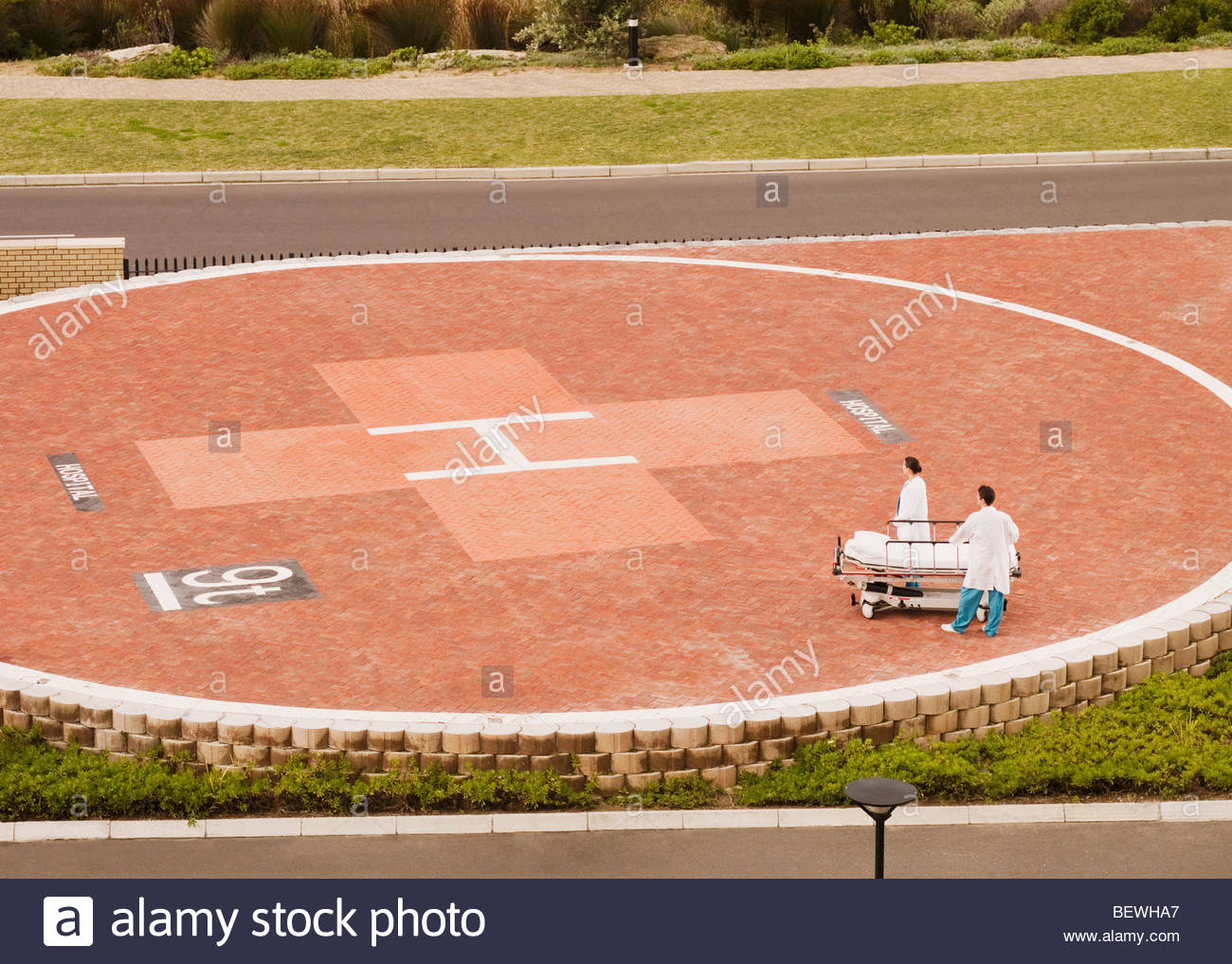 Doctors waiting for helicopter with gurney - Stock Image