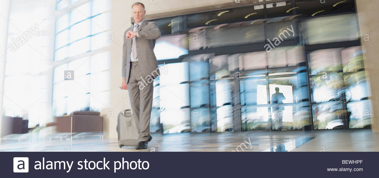Businessman with luggage checking wristwatch - Stock Image