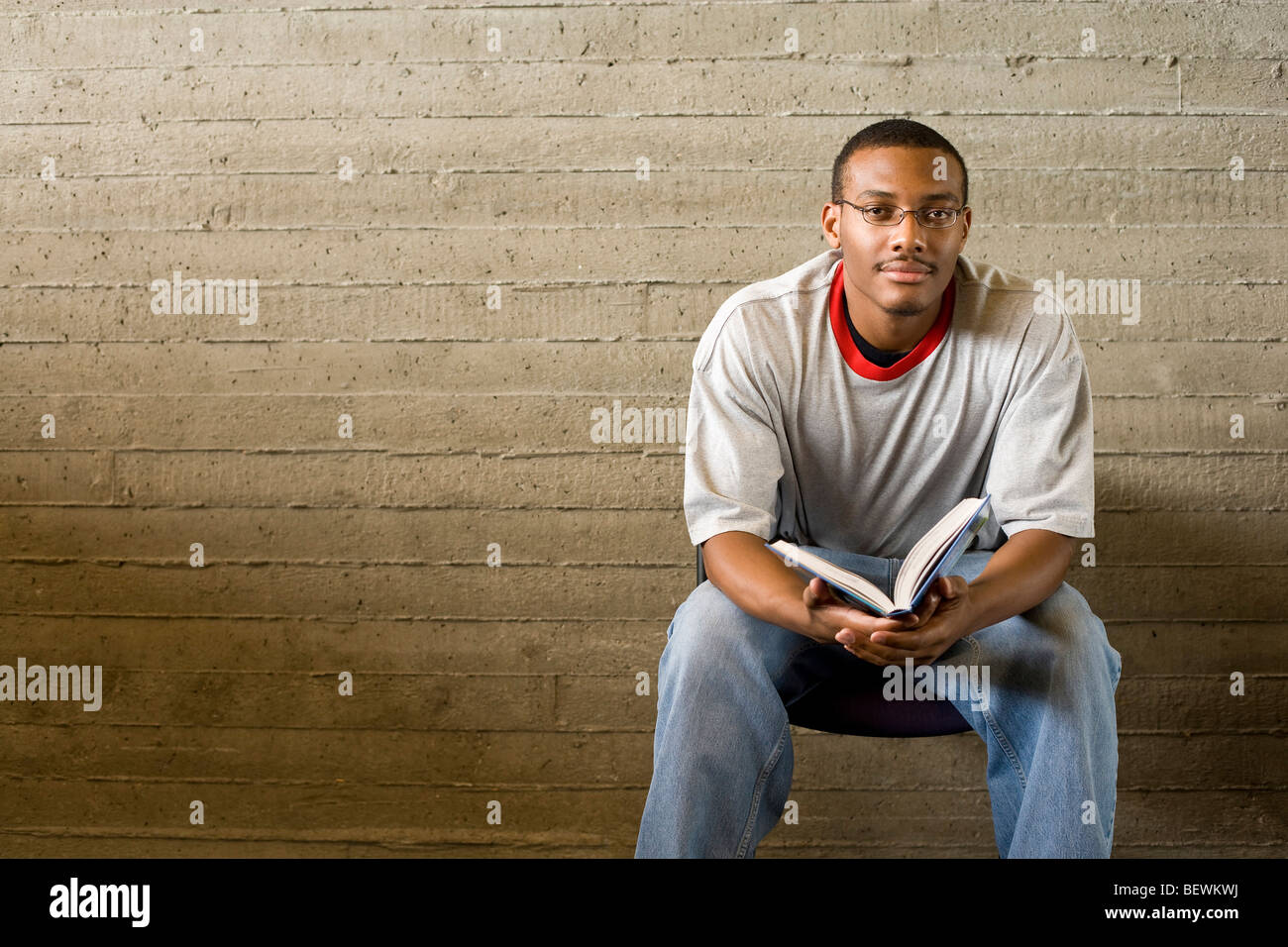 Young man reads and studies in a library - Stock Image