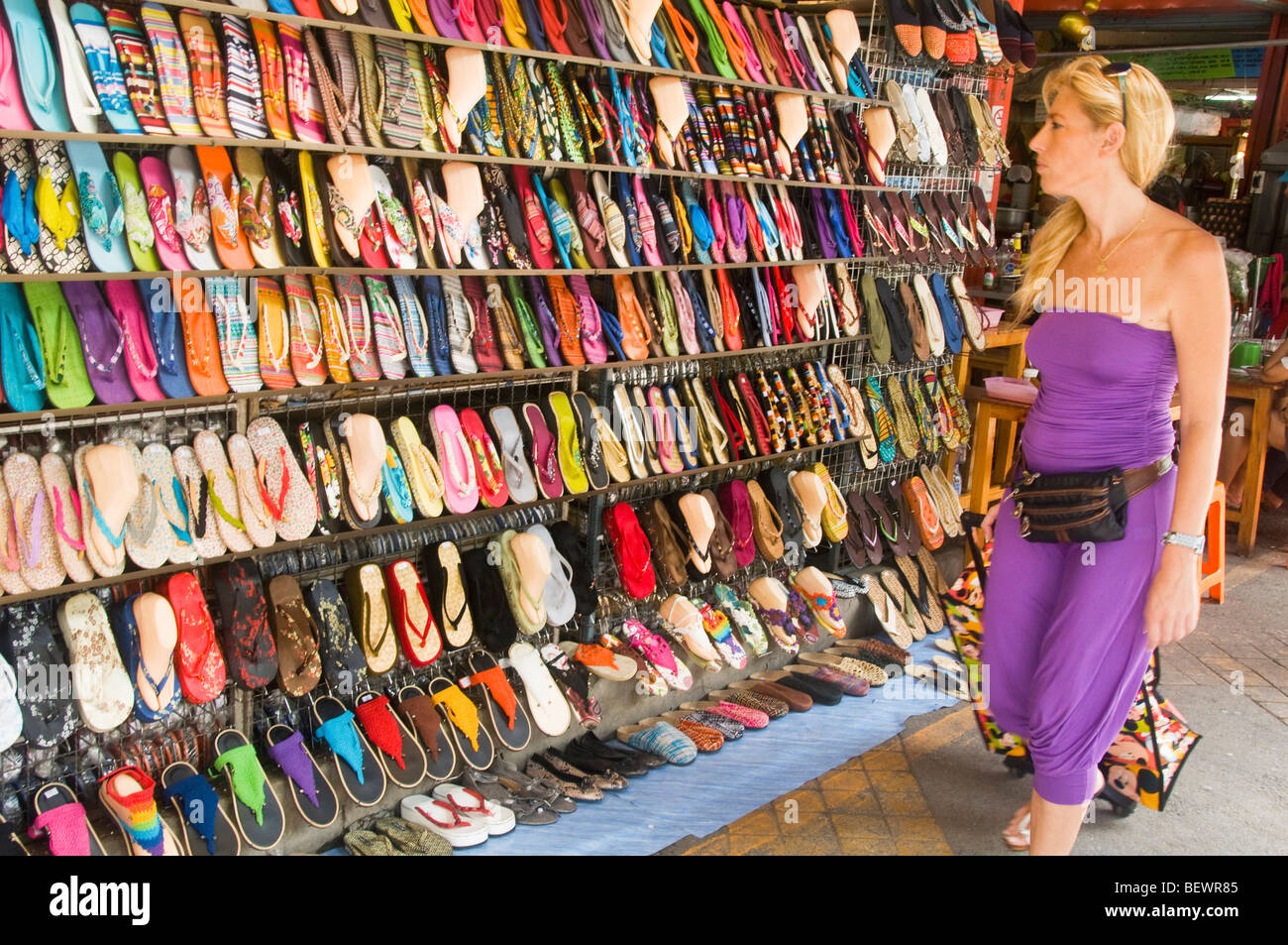 tourist shopping for shoes at the Chatuchak Weekend Market in Bangkok Thailand - Stock Image
