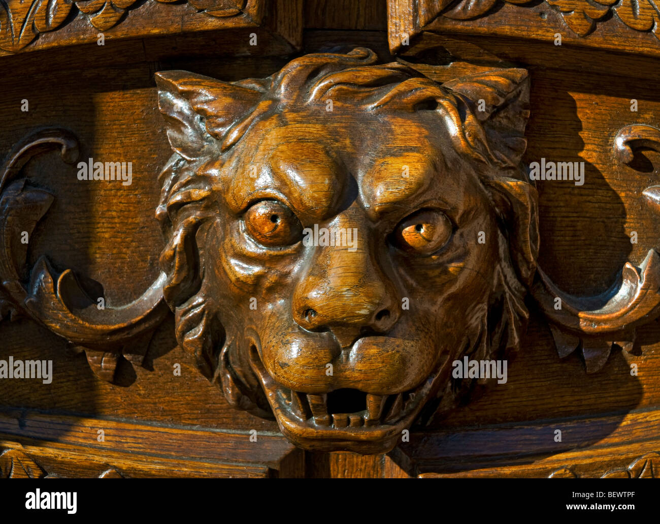 Ornate carving of mythical fierce lion as guardian on grand substantial wooden front entrance door - Stock Image