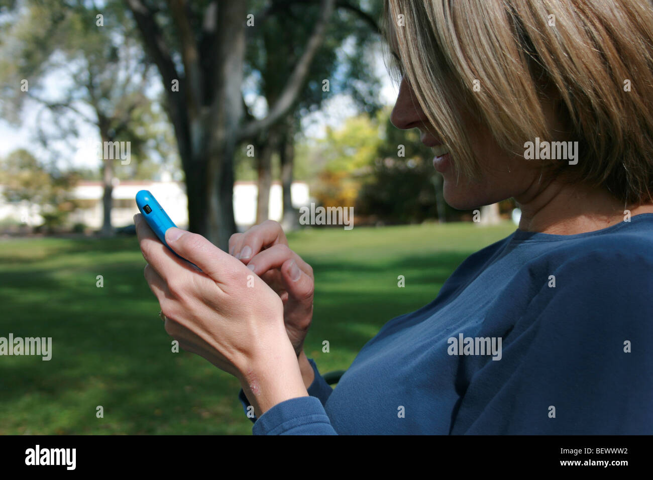 closeup of a woman using her touch screen i-phone, sitting in a park - Stock Image