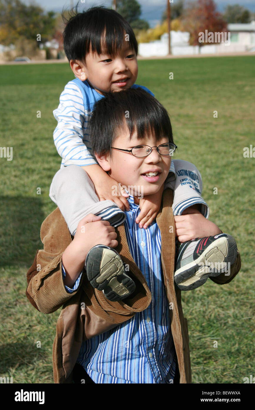 ten year old Japanese boy carries his three year old brother on his shoulders, outdoors at a park - Stock Image