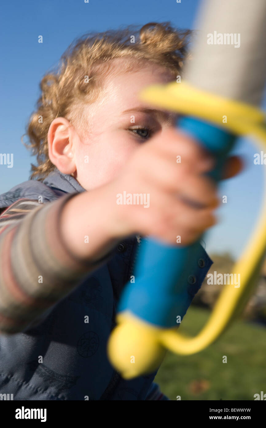 three year old boy lifting his sword, ready for pretend battle, foam sword weapon - Stock Image