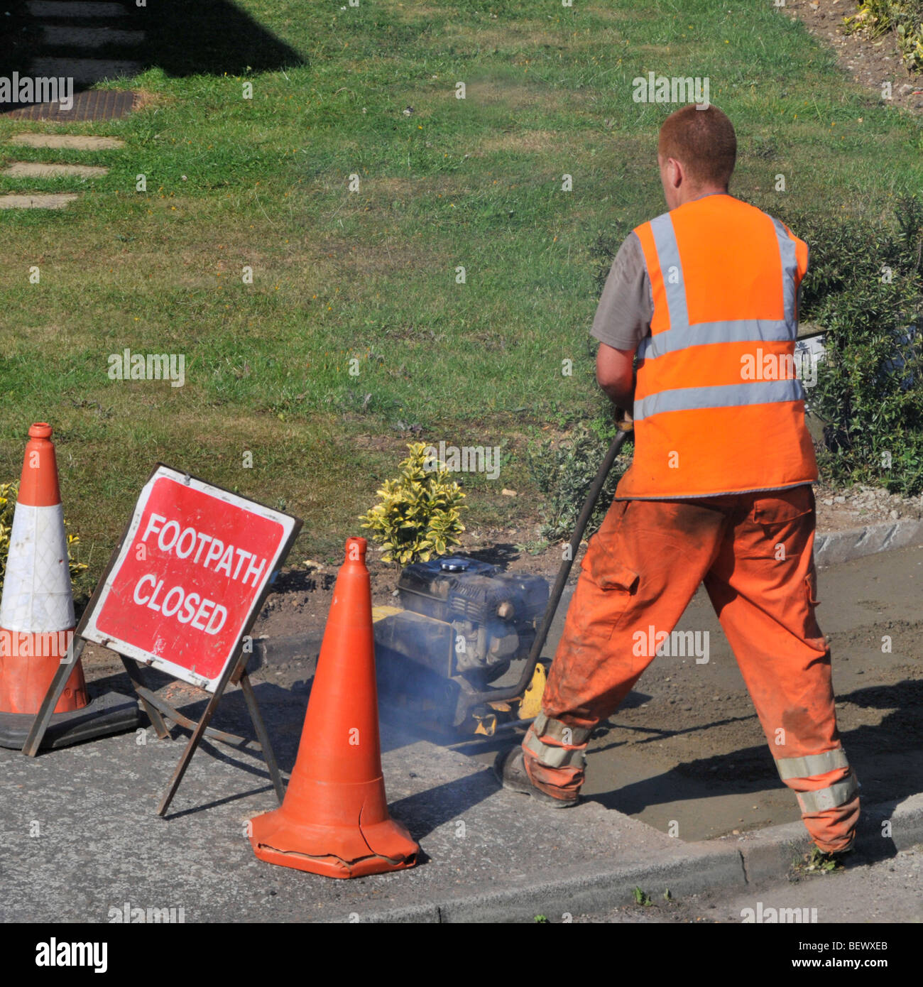 Workmen attending to footpath pavement repairs in residential street Stock Photo
