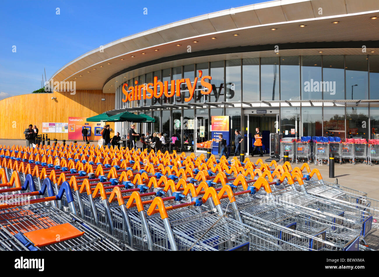 Sainsburys supermarket trolley park and entrance with Starbucks coffee shop - Stock Image