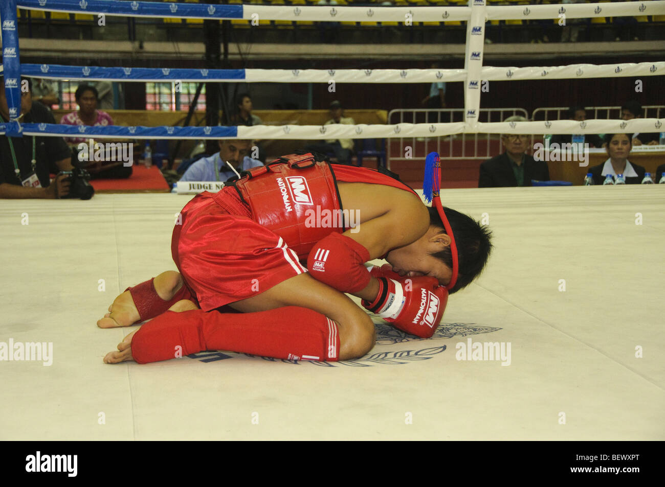 muay thai kickboxing fighter in prayer at the SE Asian Martial Arts Championships in Bangkok Thailand - Stock Image