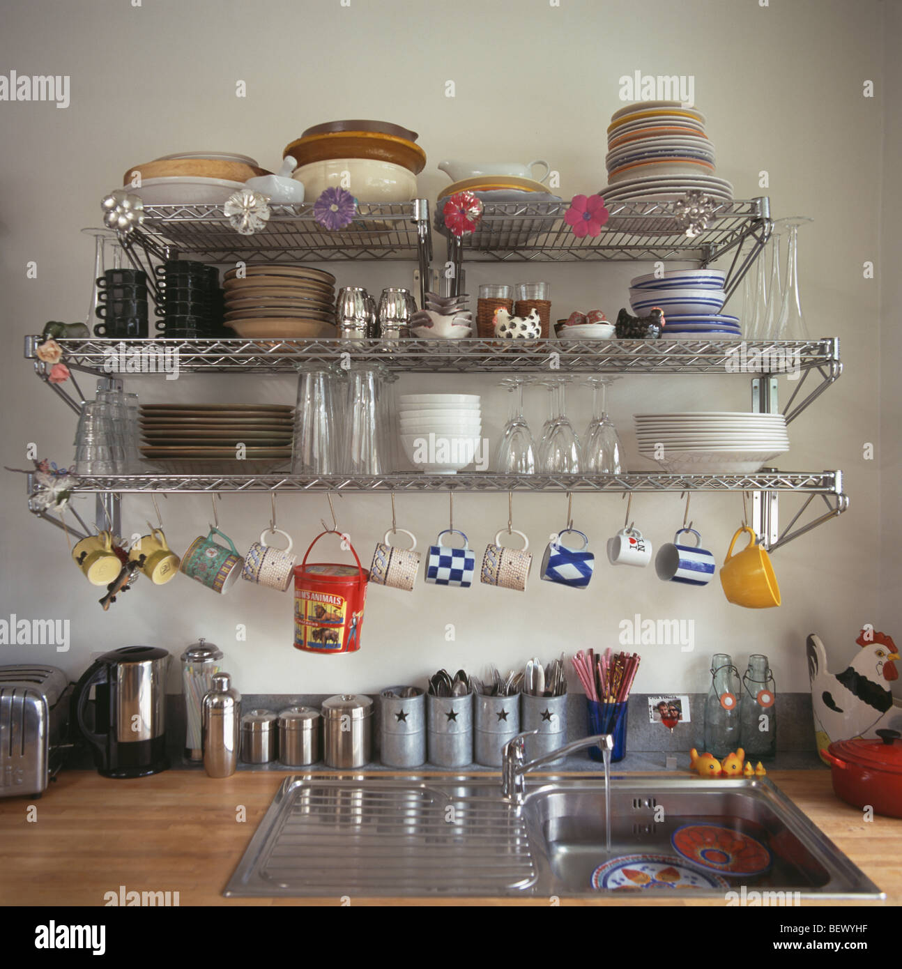 Crockery and pans on stainless steel storage shelves above stainless steel kitchen sink & Crockery and pans on stainless steel storage shelves above stainless ...