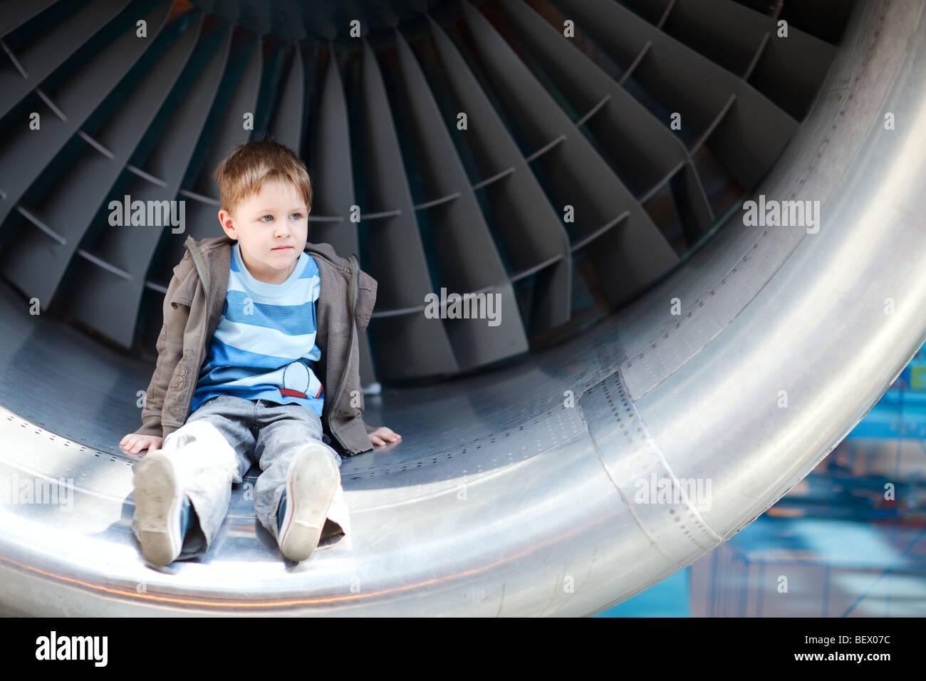 Boy sitting inside aircraft turbine - Stock Image