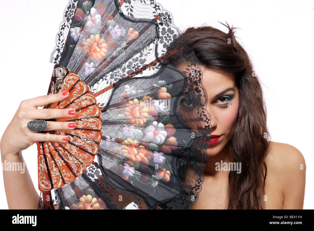 A Spanish beautiful woman behind traditional fan on white background - Stock Image