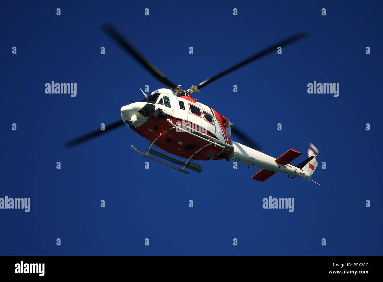 Flying helicopter in deep blue sky. Coast Guard colours. Stock Photo