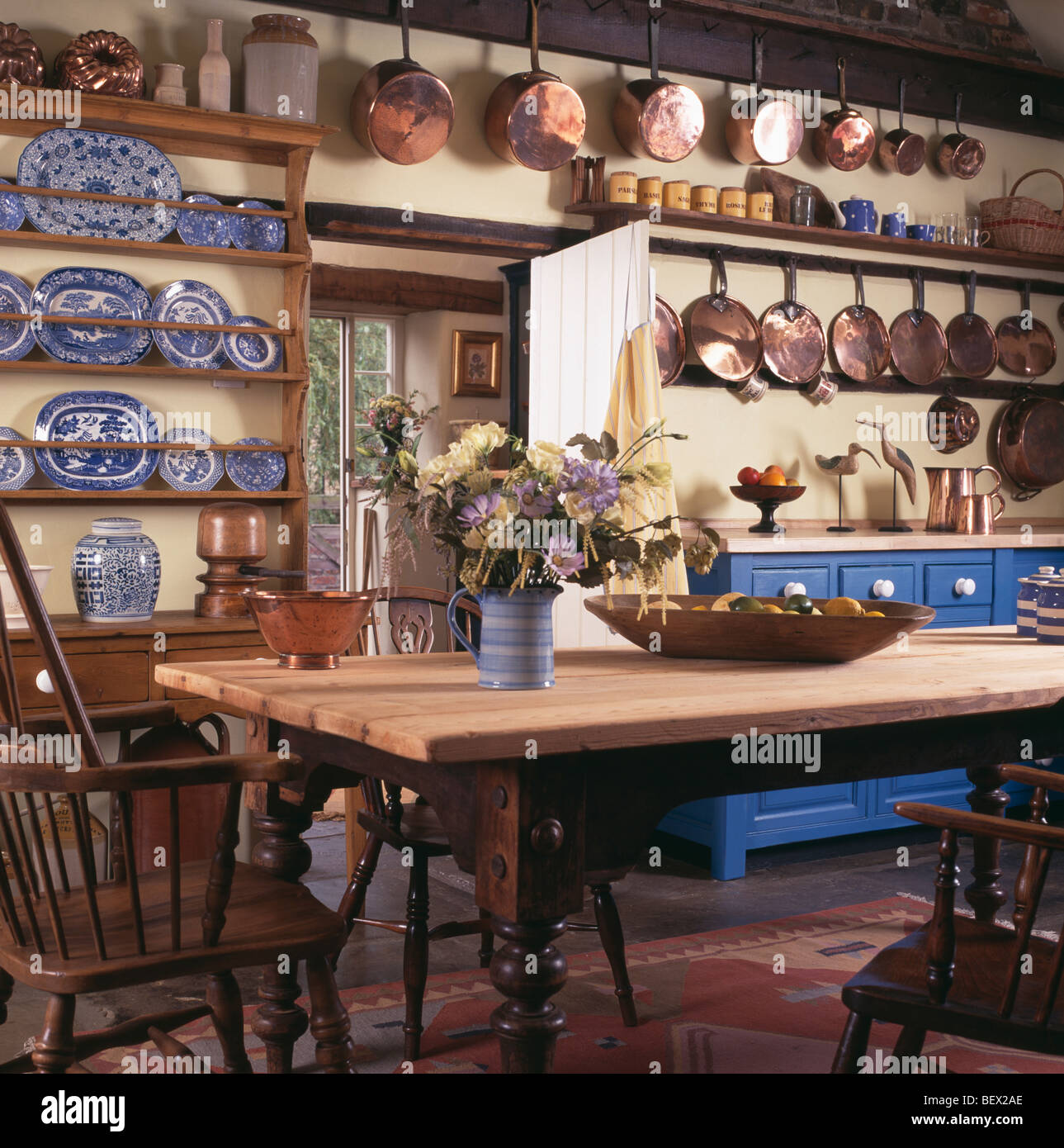 Copper pans and blue+white china on shelves in cottage dining room ...