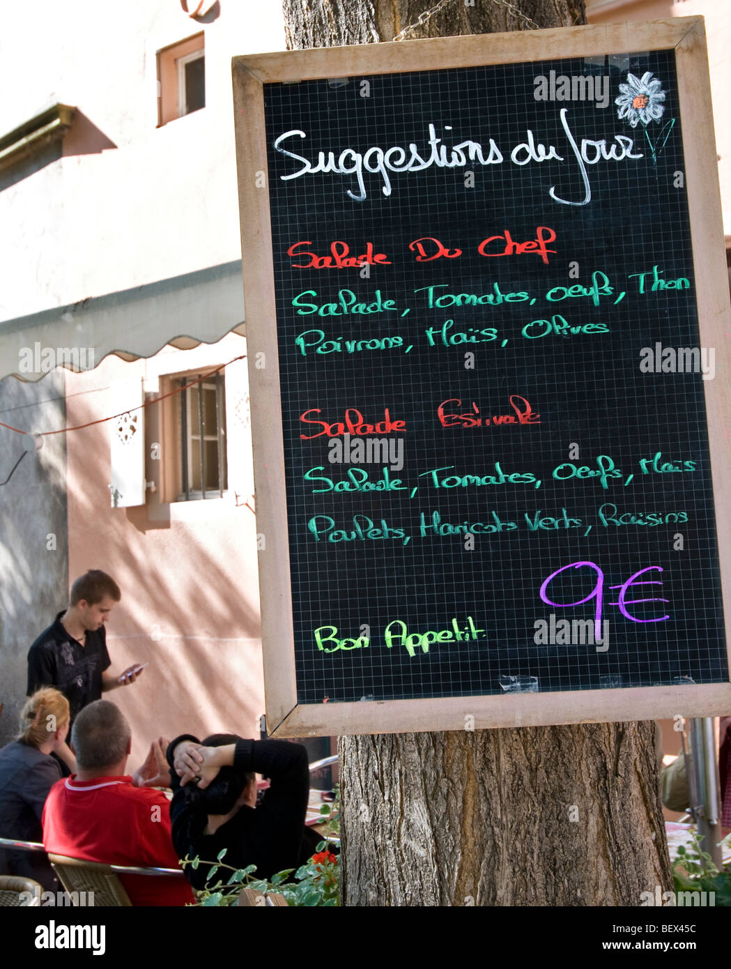 Simple inexpensive menu board waiter taking order with customers in alfresco Colmar restaurant Alsace France Stock Photo