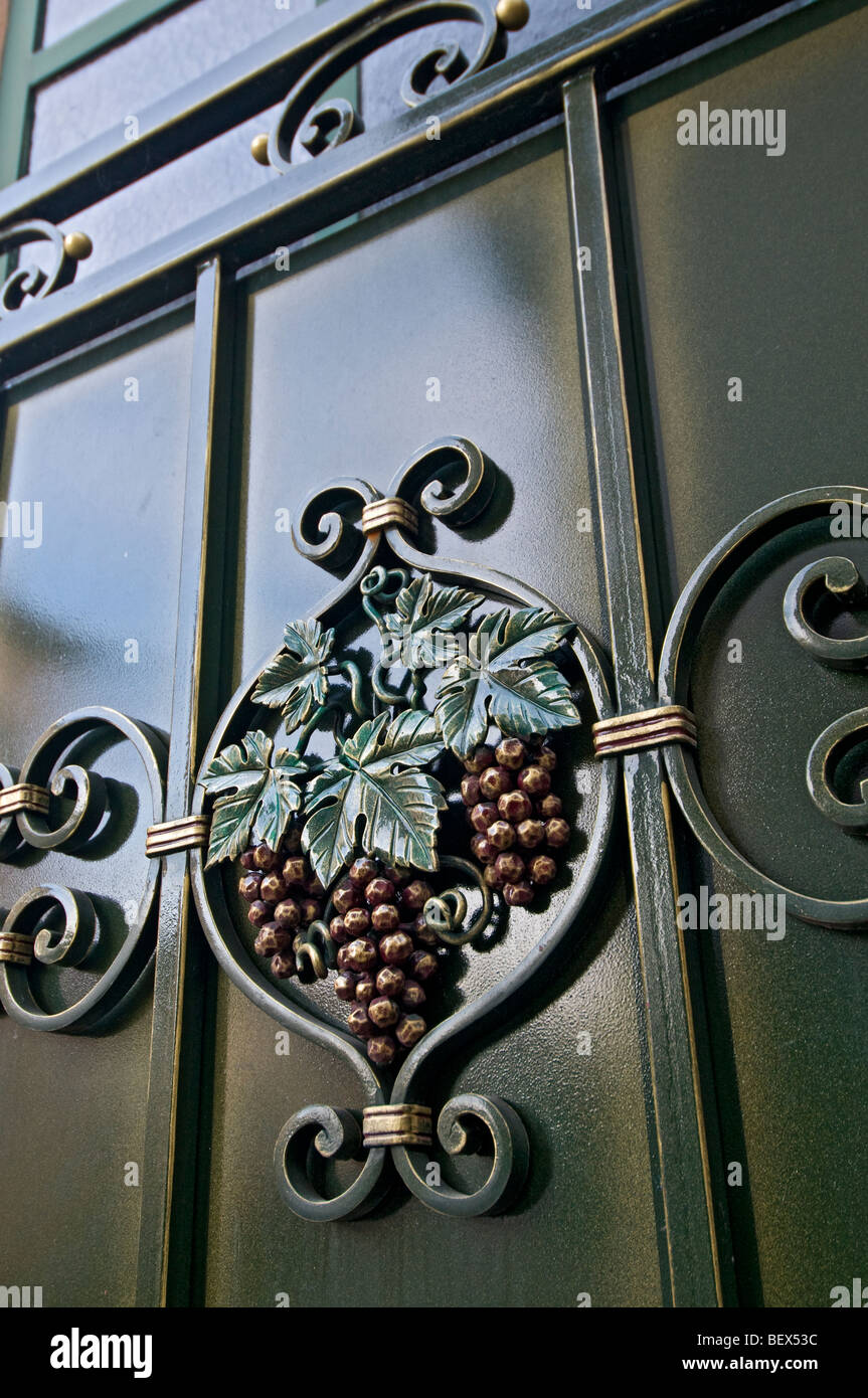Grape motif on winemakers grand entrance gateway outside winery in Eguisheim Alsace France - Stock Image