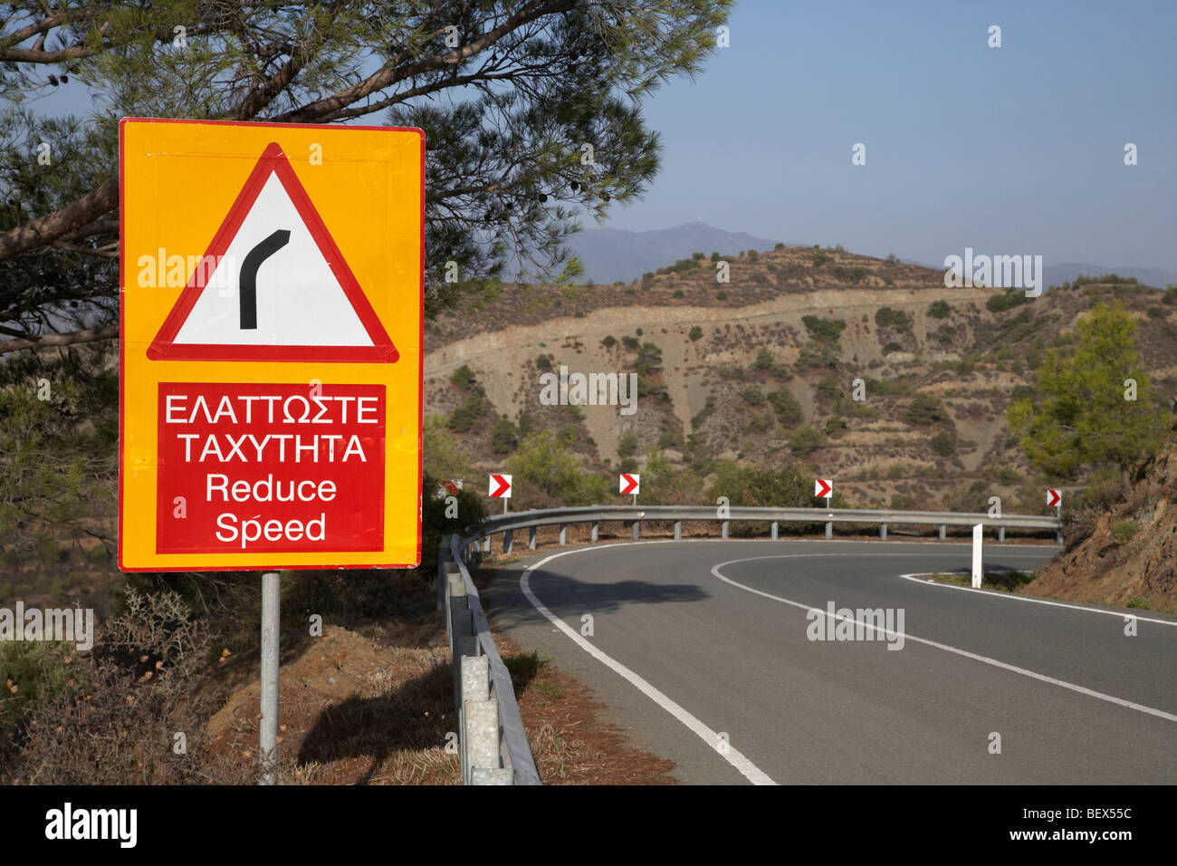 bilingual reduce speed dangerous bend sign on the f106 mountainside road near stavrovouni republic of cyprus europe - Stock Image