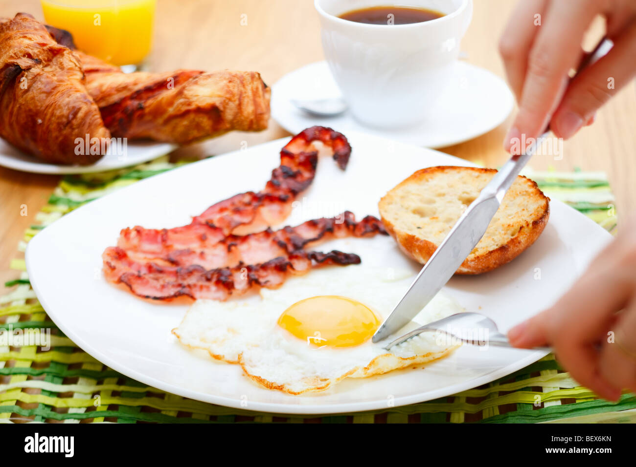 Delicious breakfast served. Corn flakes with berries, fried egg, bacon, toast, croissants, juice and fresh coffee. - Stock Image