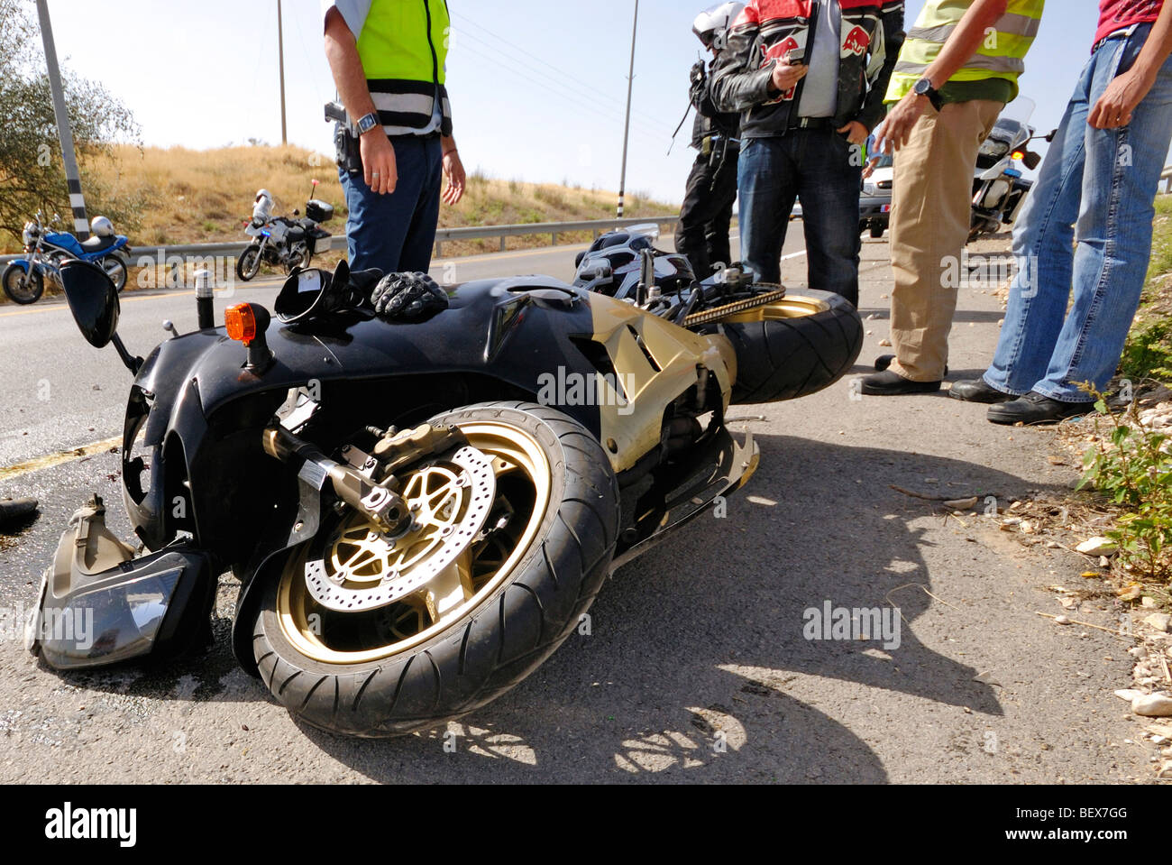 Israel, A motorbike lies on the road after a traffic collision injured person (not in view) is treated by medics - Stock Image