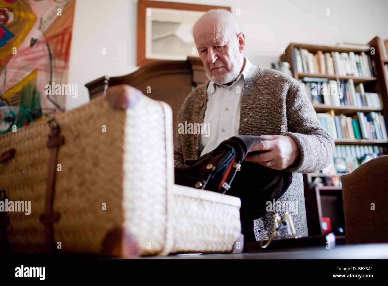 Senior packing a suitcase . - Stock Image