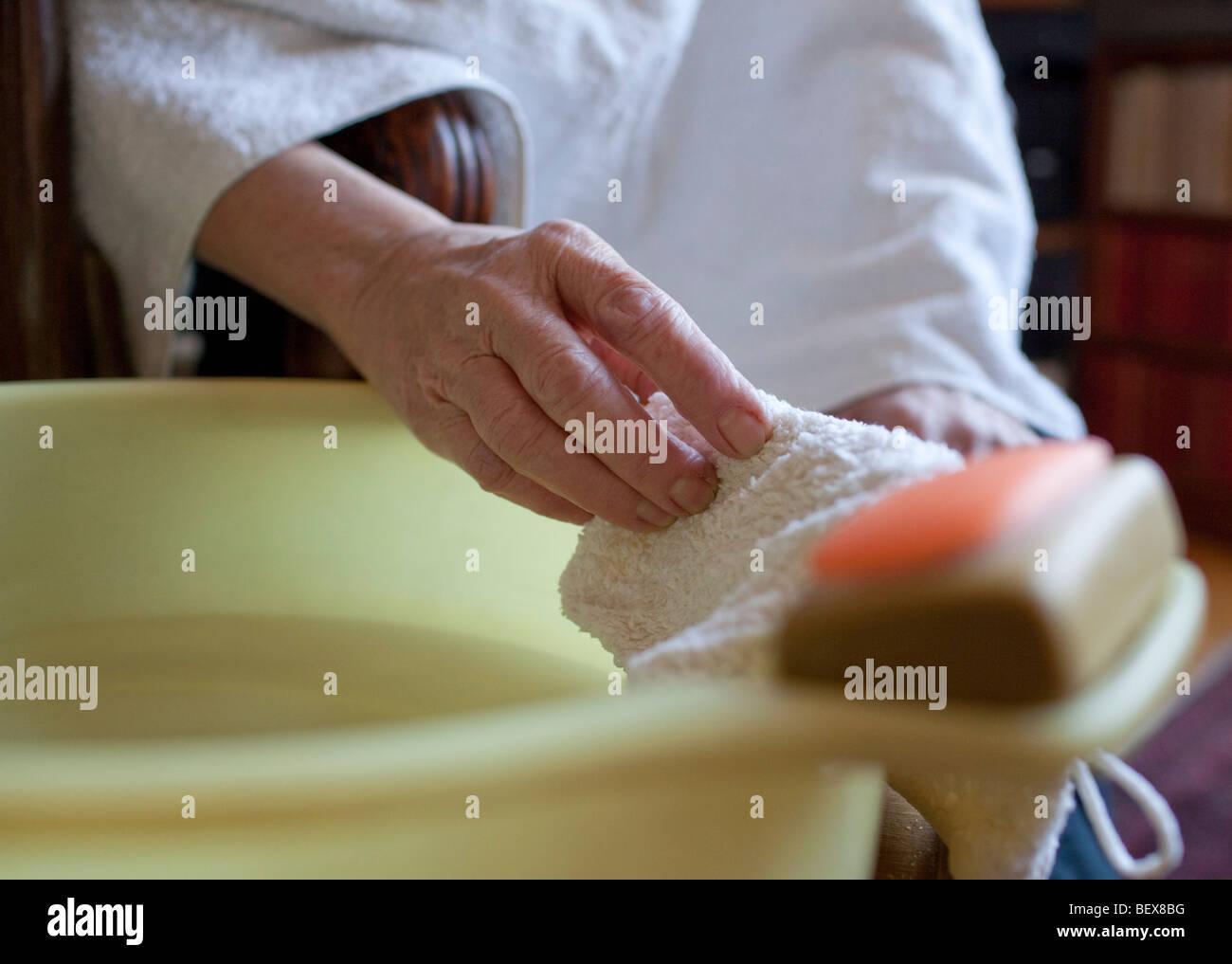 Senior is washing herself . - Stock Image