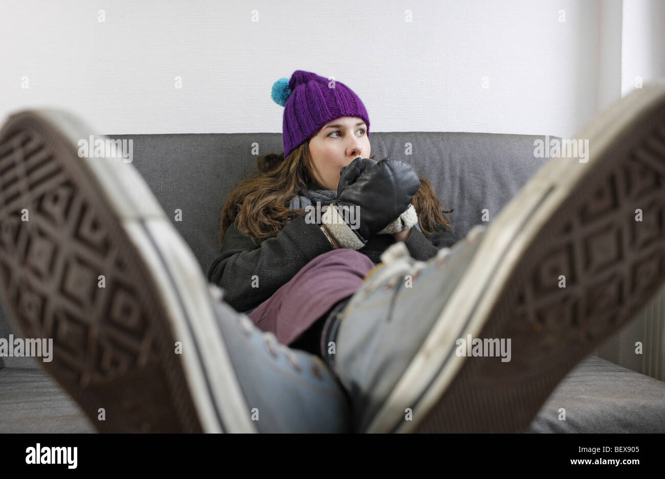 Saving heating coasts, young woman at home wearing a cap and gloves . - Stock Image